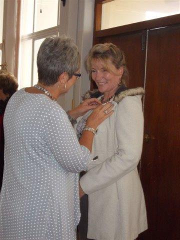 Uitgaande Sirkelvisepresident, Lorraine du Toit, steek die kenteken vir inkomende Sirkelvisepresident, Elna Botha van Hermanus, aan.